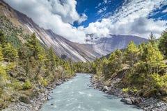 Река приходя через долину между большими горами вполне  Стоковое фото RF