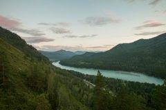 Река пропускает между горами покрытыми с лесом на Altai на заходе солнца Стоковые Фотографии RF