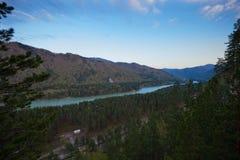 Река пропускает между горами покрытыми с лесом стоковая фотография