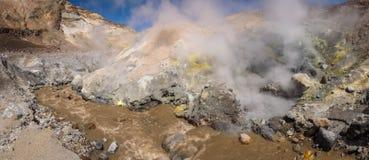 Река пропуская через каньон с фумаролами внутри кратера вулкана Mutnovsky стоковое изображение rf