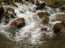 Река свежей воды среди черных утесов Поток свежего aqua быстрый в камнях Стоковые Фото