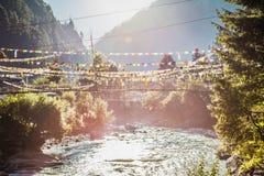 Река с висеть пешеходный мост и флаги nepalese Стоковое Изображение