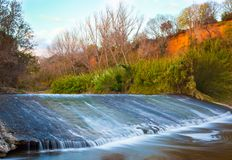 Река с утесами водопада и захода солнца накаляя стоковые изображения
