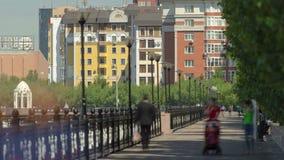 Река Ishim, люди идет на timelapse портового района, здания, предпосылки, tratuar и деревья день солнечный astana акции видеоматериалы