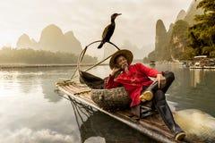 Река Li - Xingping, Китай Около январь 2016 - рыболов отдыхая с его бакланом на бамбуковом сплотке стоковые изображения
