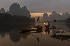 Река Li - Xingping, Китай Январь 2016 - старый рыболов получает готовым пойти вне удить с его бакланами Стоковая Фотография