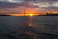Река Tagus, мост 25-ое апреля Лиссабон на заходе солнца от корабля, Португалии Стоковое Изображение