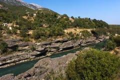 Река Vjosa в южной Албании врезанной в интересном ландшафте утеса с мостом и горами на заднем плане, Албания Стоковое Изображение RF