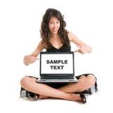 рекламирующ компьтер-книжку девушки годную к употреблению Стоковое Изображение
