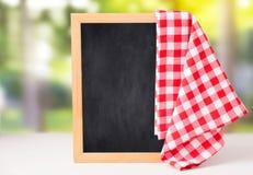 Рекордная доска с красным цветом проарретировала салфетку на таблице стоковые фотографии rf