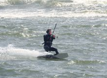 Рекреационное действие водных видов спорта Kiteboarder ехать волны Дорсет, Великобритания Май 2018 стоковые изображения
