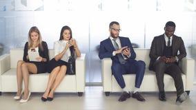 Рекрутство к компании Молодые заявителя ожидают интервью группа в составе молодые люди пробурила ждать работу стоковая фотография rf