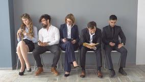 Рекрутство к компании Молодые заявителя ожидают интервью группа в составе молодые люди пробурила ждать работу акции видеоматериалы