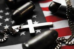 Религиозный крест золота на американском флаге с 45 автоматическими пулями личного огнестрельного оружия высококачественными Стоковое Изображение RF