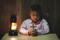 Религиозный христианский мальчик моля над библией внутри помещения стоковое изображение rf
