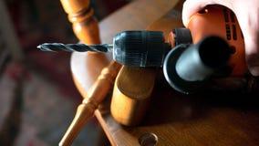 Ремонтировать деревянного стула с концом сверла вверх, части отполированной древесины и сверло при бит установленный сверх, над в Стоковое Изображение