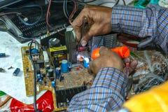 Ремонтировать и проверка старой материнской платы ТВ дома на таблице стоковая фотография rf