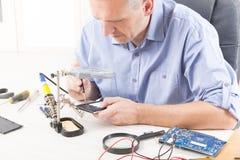 Ремонтировать мобильный телефон в электронной мастерской стоковое фото