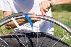 Ремонтирующ колесо велосипеда outdoors во время отключения Стоковое Изображение