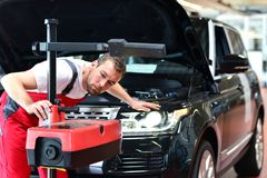 Ремонтная мастерская автомобиля - работник проверяет и регулирует фары a стоковые фото