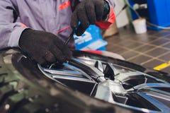 Ремонтник балансирует колесо и устанавливает безламповую автошину автомобиля на балансер в мастерской стоковые фотографии rf