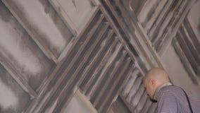 Ремонтник используя спрейер следа рассеивает краска на деревянной стене сток-видео