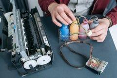 Ремонтник исправляя CISS в взгляд сверху принтера офиса Стоковые Фото