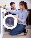 Ремонтник и женщина около стиральной машины стоковое фото