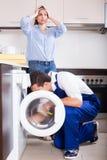 Ремонтник и женщина около стиральной машины стоковая фотография rf
