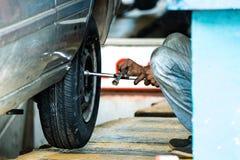 Ремонтник покрышки регулируя винты колеса a на автомобиле в Галле, Шри-Ланка стоковая фотография rf