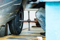 Ремонтник покрышки регулируя винты колеса a на автомобиле в Галле, Шри-Ланка стоковая фотография