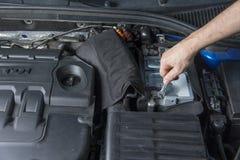 Ремонтник с ключем проверяя контакты автомобильного аккумулятора стоковая фотография rf