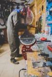 Ремонты темы и обслуживание лыж Мужской работник ремонтирует рабочую одежду, прикладывая воск на сползая поверхности на лыжи стоковое фото rf