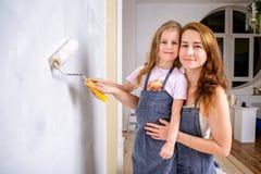 Ремонт в квартире Счастливая мать семьи и маленькая дочь в голубых рисбермах красят стену с белой краской Мама и дочь стоковое фото rf