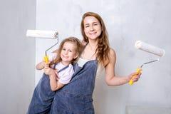Ремонт в квартире Счастливая мать семьи и маленькая дочь в голубых рисбермах красят стену с белой краской Мама и дочь стоковая фотография rf