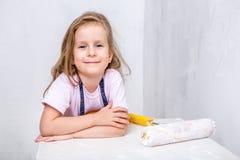 Ремонт в квартире Счастливая мать семьи и маленькая дочь в голубых рисбермах красят стену с белой краской Девушка приняла a стоковое изображение
