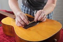 Ремонт гитары и обслуживание - гайка моста работника меля Стоковое фото RF