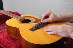 Ремонт гитары и обслуживание - гайка сервопривода моста работника меля Стоковое Изображение