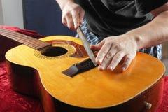 Ремонт гитары и обслуживание - меля гайка моста Стоковое фото RF