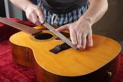 Ремонт гитары и обслуживание - меля гайка моста Стоковые Изображения