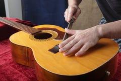 Ремонт гитары и обслуживание - меля гайка моста Стоковая Фотография