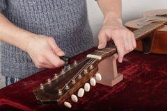 Ремонт гитары и обслуживание - починка работника новые строки Стоковое Фото