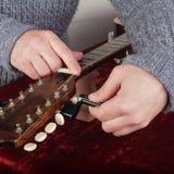 Ремонт гитары и обслуживание - починка работника новые строки Стоковая Фотография