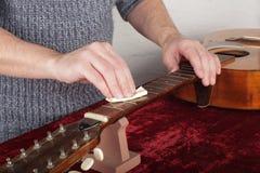 Ремонт гитары и обслуживание - увлажнять работника и вкрапленность o Стоковое Фото