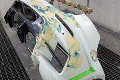 Ремонт заднего бампера белого автомобиля после аварии с помощью пестротканой замазке в мастерской для красить стоковое фото