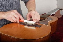 Ремонт и обслуживание гитары - работник точит мост s специального инструмента Стоковое Изображение