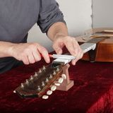 Ремонт и обслуживание гитары - работник точит мост s специального инструмента Стоковые Фотографии RF