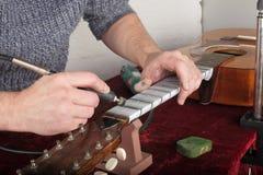 Ремонт и обслуживание гитары - шея гитары работника полируя волнуется d стоковое изображение