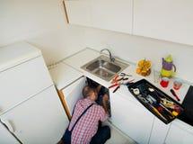 Ремонт рабочего класса пускает по трубам на раковине в кухне Стоковая Фотография RF