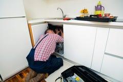 Ремонт разнорабочего пускает по трубам на раковине в кухне Стоковые Фото